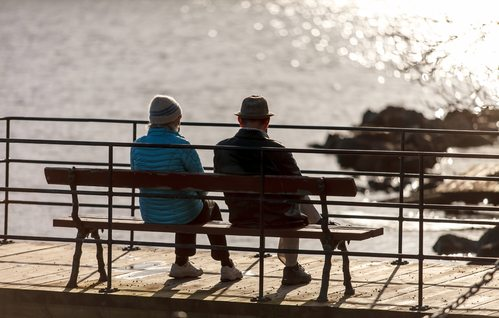 elderly couple sitting on bench near ocean/lake