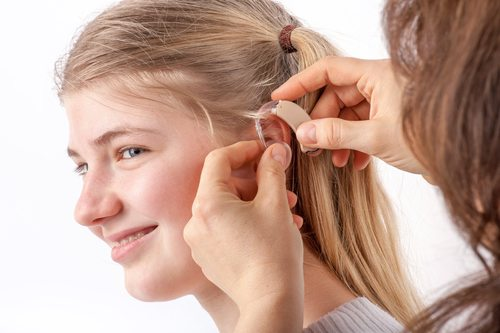 Woman inserting a hearing aid into a young girl's ear in front of a white background